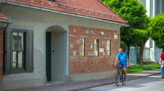 Two people on bicycles are passing by Plecnik House Stock Footage