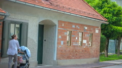 Two people are passing by Plecnik House Stock Footage