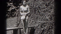 1938: woman wearing bathing suit holds swim cap then steps over railing  Stock Footage