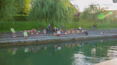 Workshop for painters on the riverbank alongside the river Ljubljanica Stock Footage