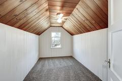 Small empty attic room with wood paneling, carpet floor and vaulted ceiling.  Stock Photos