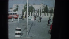 1976: a busy cross road at the side of the building with busy people Stock Footage