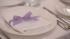 White serviette with violet ribbon lies on dinner plate Stock Footage