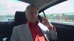 Old - aged boss has phone conversation with business partner on the way to work Stock Footage