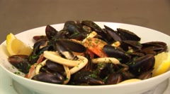 Plate with prepared mussels in white wine with lemon, prawns and basil. Fresh Stock Footage