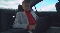 Middle aged man using laptop in the car sits on the back seat Stock Footage