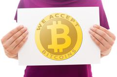 Girl holding white paper sheet with Bitcoin logo Stock Photos
