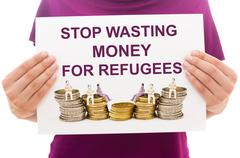 Girl holding white paper sheet with text Stop wasting money for refugees Stock Photos