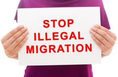 Girl holding white paper sheet with text Stop illegal migration Stock Photos