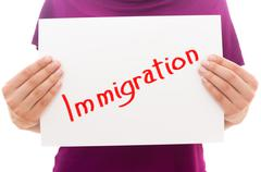Girl holding white paper sheet with text Immigration Stock Photos