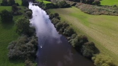 Aerial view of a river twith people walking in a field in the distance. Stock Footage