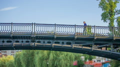 Two people are crossing the bridge and going to the opposite directions Stock Footage