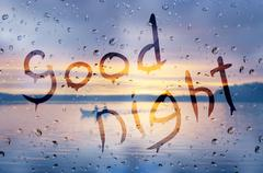 Rain on glass with Good night text Stock Photos