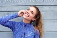 Happy woman standing with headphones listening to song Stock Photos