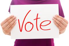 Girl holding white paper sheet with text Vote Stock Photos