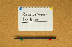 Read between the lines text note message pin on bulletin board Stock Photos