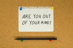 Are you out of your mind text note message pin on bulletin board Stock Photos