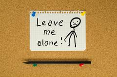 Leave me alone text note message pin on bulletin board Stock Photos
