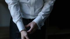 Man adjusts his sleeves in dark room Stock Footage