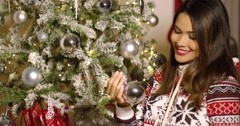 Pretty woman decorating an Xmas tree with baubles Stock Footage