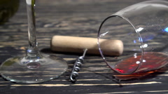 Corkscrew, cork, bottle and glass of red wine on a wooden table Stock Footage