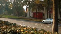 Car drives along autumn street Stock Footage