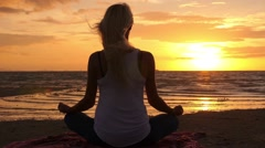 Woman Meditating at Sunset Beach in Lotus Pose Stock Footage