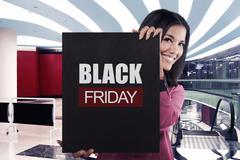 Smiling asian girl holding black banner sale with BLACK FRIDAY message Kuvituskuvat