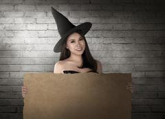 Beautiful smiling asian woman with hat in the witch costume holding paper Stock Photos