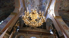 Shiny chandelier hangs from the painted ceiling in church Stock Footage
