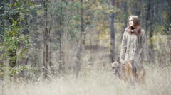 Young attractive woman walking in autumn forest with her pet - german shepherd Stock Footage