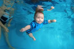 The little boy in overalls swims underwater in swimming pool Stock Photos