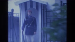 1976: young guard stands stoically at his post as a pair walks by Stock Footage