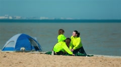 Young scouts and the coach set a tent on the shore of the lake Stock Footage