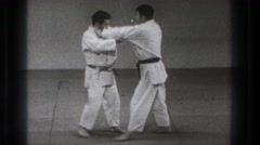 1965: two karatekas dispute a match on the tatami and one is thrown to the floor Stock Footage
