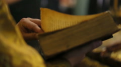 Priest holds old Bible in his hands Stock Footage