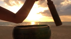 Yogi Woman Plays on Tibetan Singing Bowl at Sunset on Beach Stock Footage