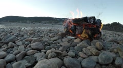 Warming birch fire by frozen river shore in late autumn morning with mountain Stock Footage