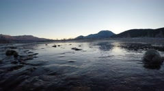 Majestic and serene late autumn river landscape with frozen shore and mountain Stock Footage