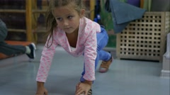 Cute kid doing stretching and gymnastics exercises at sports hall Stock Footage