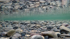 Colorful river bottom in late autumn with algae covered stones and reflection Stock Footage