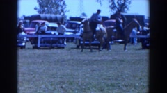 1957: several people on horseback are observed by others who wander around Stock Footage