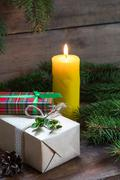 Christmas gifts and lighted candle Stock Photos