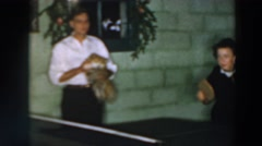 1957: two ladies playing ping pong while a man holds a small dog WHEELING OHIO Stock Footage