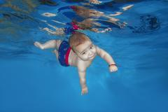 Little boy learning to swim under water in the pool Kuvituskuvat