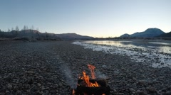 Beautiful campfire on cold frozen river shore in early autumn morning Stock Footage