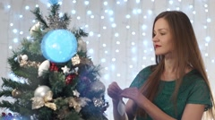 Playful sexy woman with red lipstick dresses up Christmas tree, admiring the Stock Footage