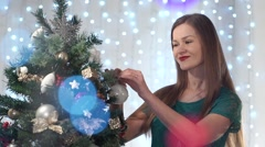 Beautiful sexy woman with red lipstick dresses up Christmas tree, cute smiles Stock Footage