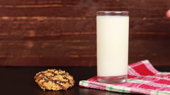 Young man drinking milk and cookie on a wooden background Stock Footage