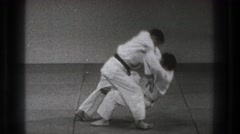 1971: two men wearing white are doing a karate move on each other on the floor. Stock Footage